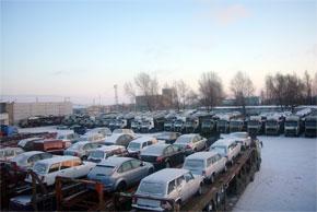 Автовозы на стоянке с легковыми автомобилями